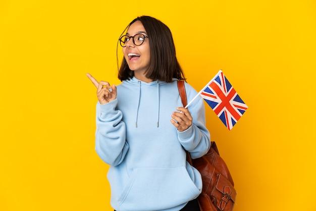 손가락을 들어 올리는 동안 솔루션을 실현하려는 노란색 배경에 고립 된 영국 국기를 들고 젊은 라틴 여자