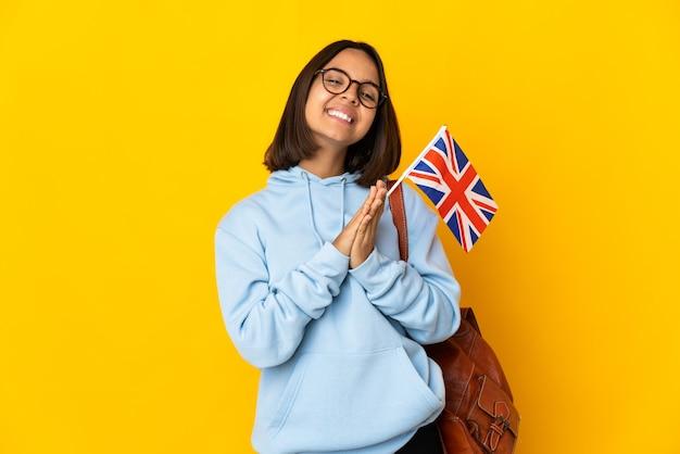 黄色の背景で隔離のイギリス国旗を保持している若いラテン女性は、手のひらを一緒に保ちます。人は何かを求めます