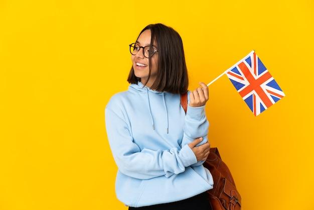 横を見て笑っている黄色の背景に分離されたイギリスの旗を保持している若いラテン女性
