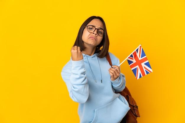 이탈리아 제스처를 만드는 노란색 배경에 고립 된 영국 국기를 들고 젊은 라틴 여자