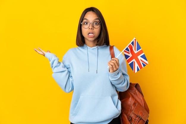 전화 제스처를 만들고 의심하는 노란색 배경에 고립 된 영국 국기를 들고 젊은 라틴 여자