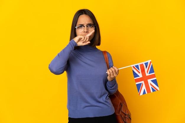 行為を停止するために彼女の手で停止ジェスチャーをしている黄色の背景に分離されたイギリスの旗を保持している若いラテン女性