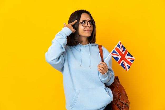 Молодая латинская женщина держит флаг соединенного королевства на желтом фоне, делая жест безумия, положив палец на голову