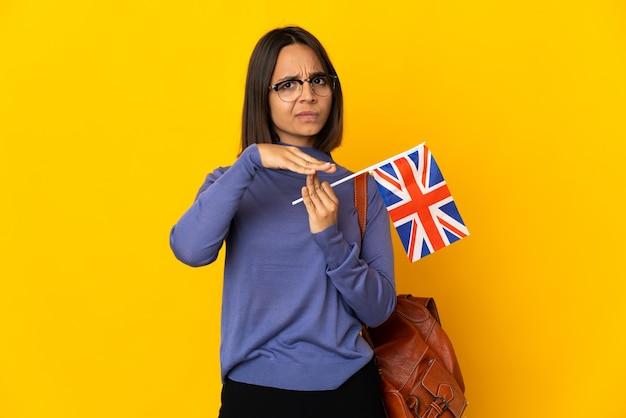 시간 초과 제스처를 만드는 노란색 배경에 고립 된 영국 국기를 들고 젊은 라틴 여자
