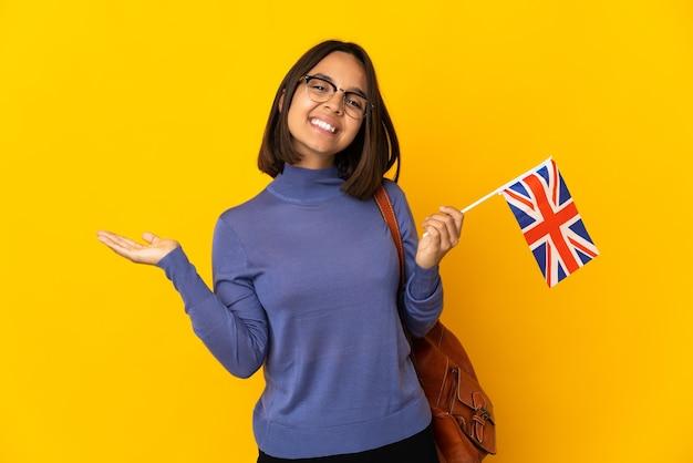 Молодая латинская женщина держит флаг соединенного королевства, изолированную на желтом фоне, представляя идею, улыбаясь в сторону