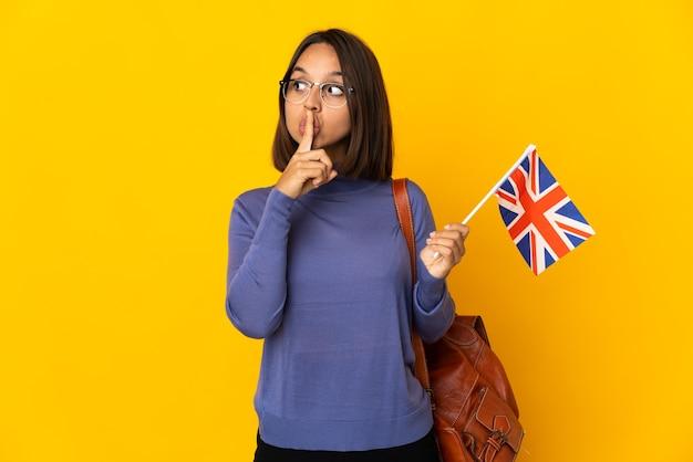 口に指を入れて沈黙のジェスチャーの兆候を示す黄色の背景に分離されたイギリスの旗を保持している若いラテン女性
