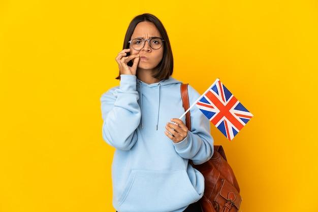 沈黙のジェスチャーの兆候を示す黄色の背景に分離されたイギリスの旗を保持している若いラテン女性