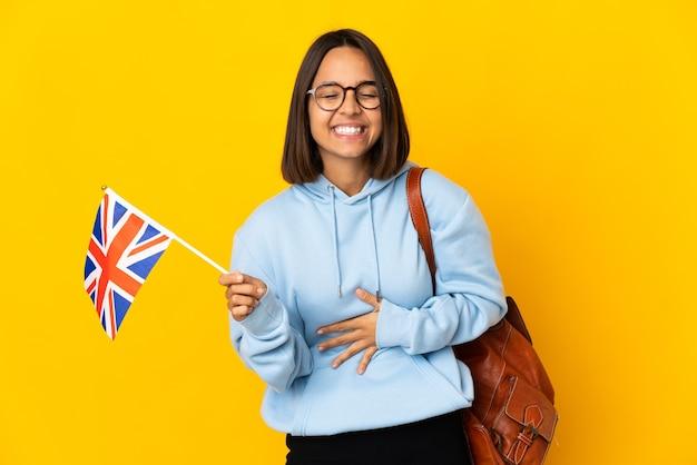 たくさん笑って黄色の背景に分離されたイギリスの旗を保持している若いラテン女性