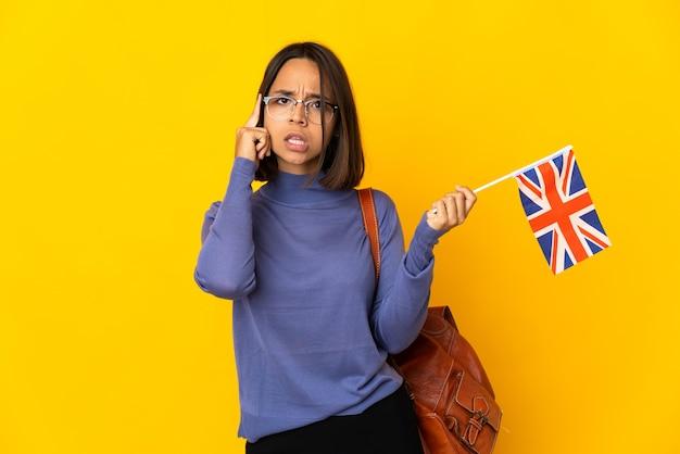 アイデアを考えて黄色の背景に分離されたイギリスの旗を保持している若いラテン女性