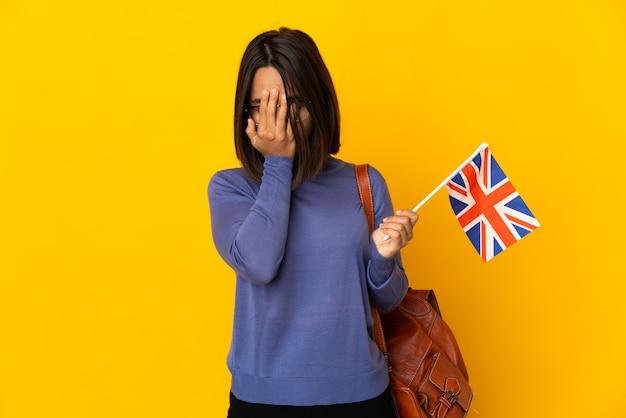 Молодая латинская женщина держит флаг соединенного королевства на желтом фоне с усталым и больным выражением лица
