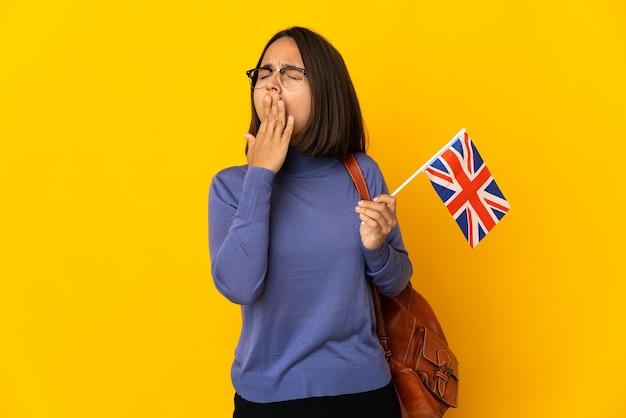 あくびをし、手で大きく開いた口を覆う黄色の背景に分離されたイギリスの旗を保持している若いラテン女性