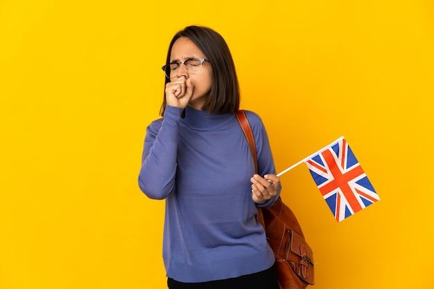 많은 기침 노란색 벽에 고립 된 영국 국기를 들고 젊은 라틴 여자