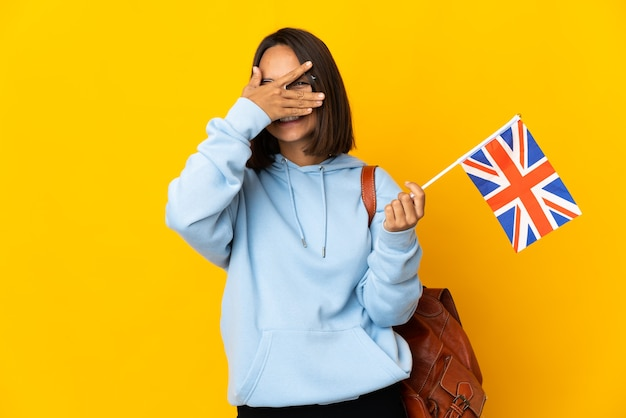 Молодая латинская женщина, держащая флаг соединенного королевства, изолированная на желтой стене, закрывает глаза руками и улыбается