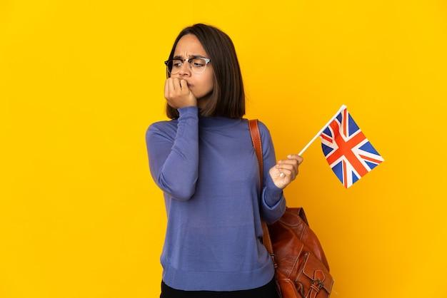 Молодая латинская женщина, держащая флаг соединенного королевства, изолированная на желтой стене с сомнениями