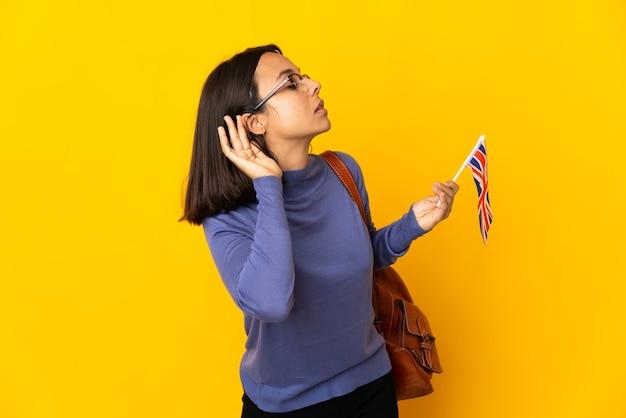 귀에 손을 넣어 뭔가를 듣고 노란색 벽에 고립 된 영국 국기를 들고 젊은 라틴 여자