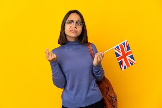 Молодая латинская женщина держит флаг соединенного королевства, изолированную на желтой стене, делает денежный жест, но разрушена