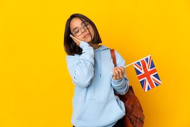 Молодая латинская женщина держит флаг соединенного королевства, изолированную на желтой стене, делая жест сна в благородном выражении