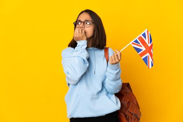 Молодая латинская женщина, держащая флаг соединенного королевства, изолированная на желтой стене, нервничала и испугалась, прикладывая руки ко рту