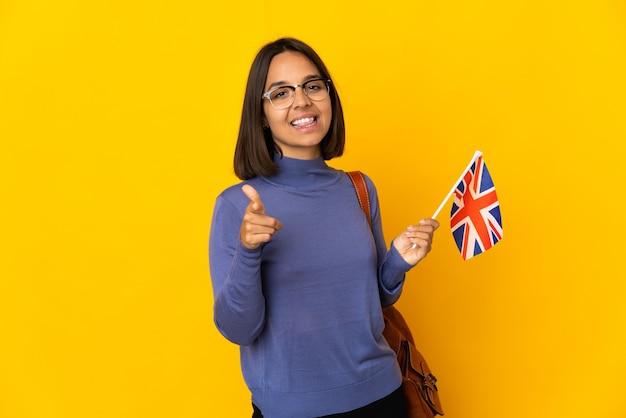 Молодая латинская женщина держит флаг соединенного королевства, изолированную на желтой стене, указывая вперед и улыбаясь