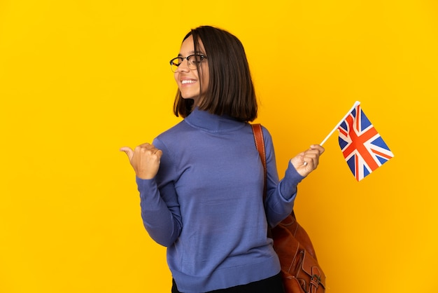 Молодая латинская женщина держит флаг соединенного королевства, изолированную на желтой стене, указывая в сторону, чтобы представить продукт
