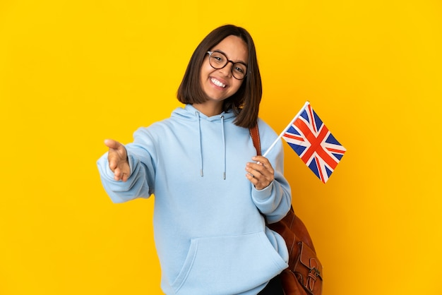Молодая латинская женщина держит флаг соединенного королевства, изолированную на желтой стене, представляет и приглашает протянуть руку