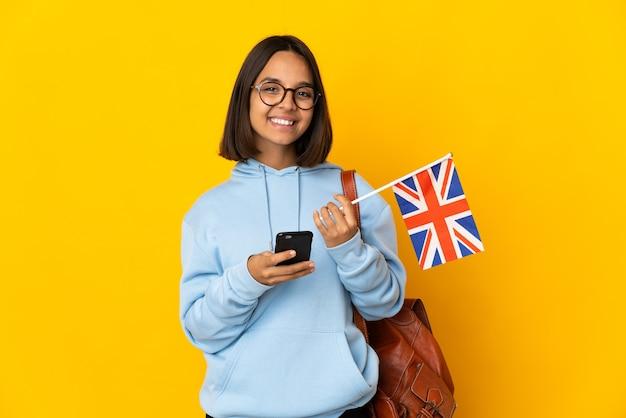 모바일로 메시지를 보내는 노란색 벽에 고립 된 영국 국기를 들고 젊은 라틴 여자