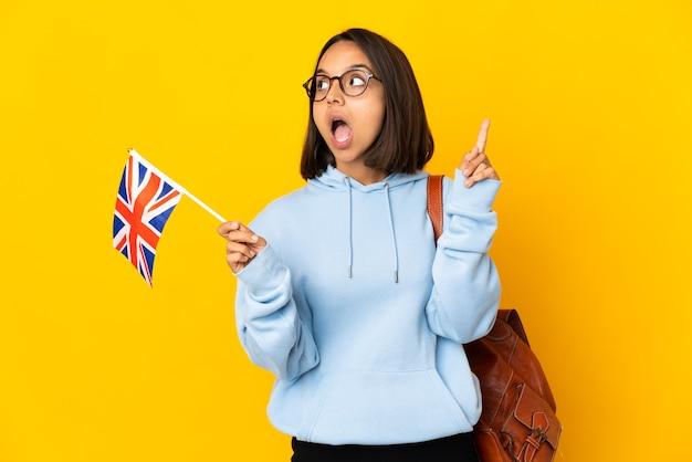 Молодая латинская женщина, держащая флаг соединенного королевства, изолированная на желтой стене, думает о идее, указывая пальцем вверх