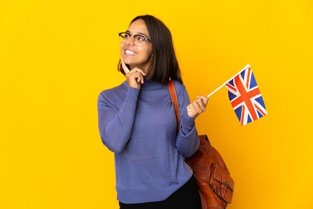 Молодая латинская женщина, держащая флаг соединенного королевства, изолированная на желтой стене, думает об идее, глядя вверх