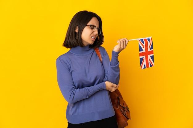 Молодая латинская женщина держит флаг соединенного королевства, изолированную на желтой стене с болью в локте