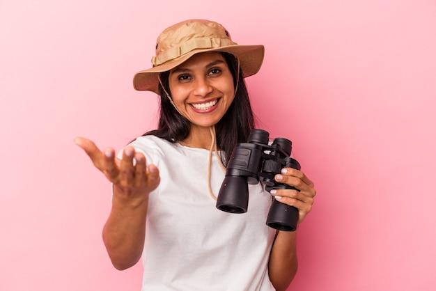 ピンクの背景に分離された双眼鏡を持っている若いラテン女性は、嬉しい驚きを受け取り、興奮し、手を上げます。