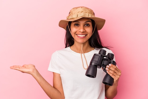 ピンクの背景に分離された双眼鏡を持っている若いラテン女性は、手のひらにコピースペースを示し、腰に別の手を保持しています。