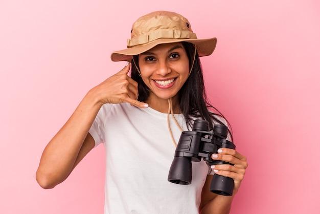 指で携帯電話の呼び出しジェスチャーを示すピンクの背景に分離された双眼鏡を保持している若いラテン女性。