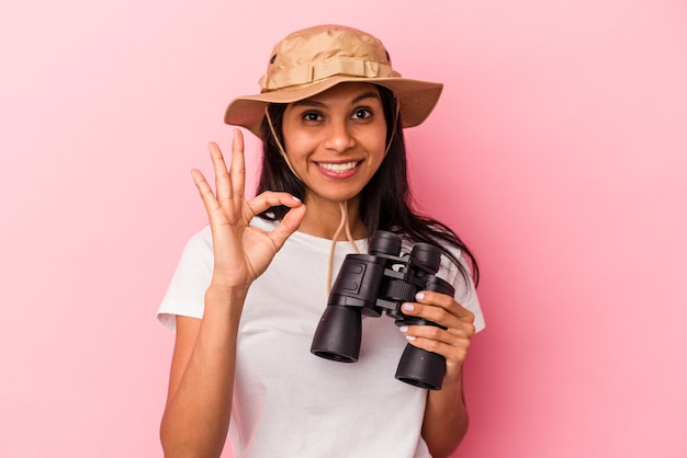Young latin woman holding binoculars isolated on pink background cheerful and confident showing ok gesture.