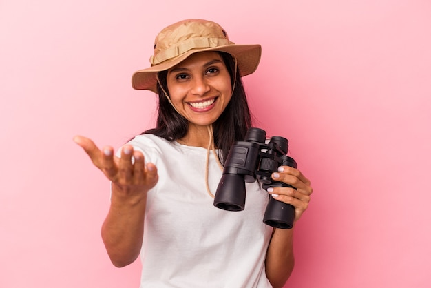 Young latin woman holding binoculars isolated on pink background receiving a pleasant surprise, excited and raising hands.
