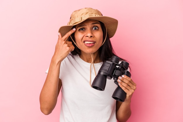 Young latin woman holding binoculars isolated on pink background showing a disappointment gesture with forefinger.