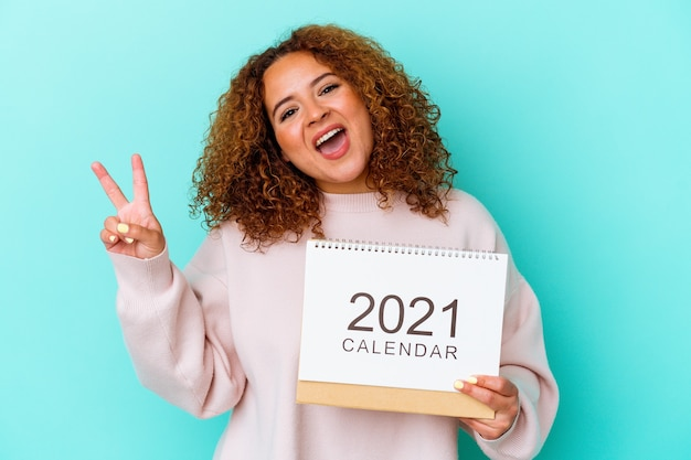 Young latin woman holding a calendary isolated on blue background joyful and carefree showing a peace symbol with fingers.
