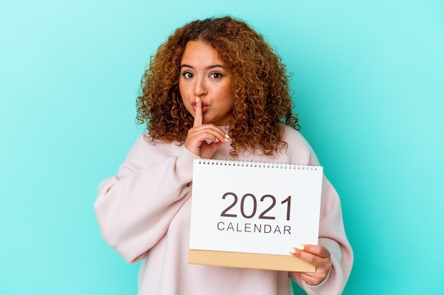 Young latin woman holding a calendary isolated on blue background keeping a secret or asking for silence.