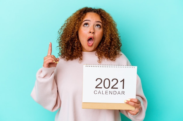 Young latin woman holding a calendary isolated on blue background pointing upside with opened mouth.