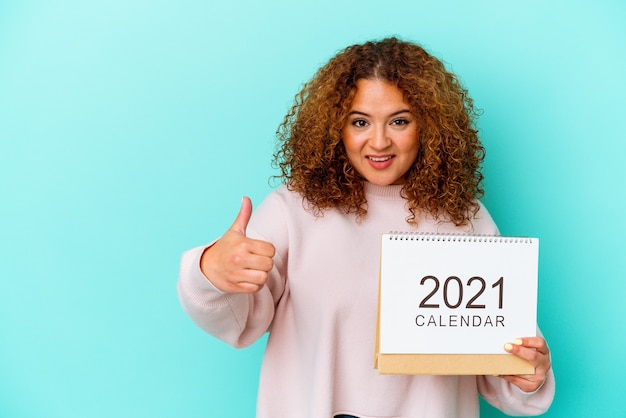 Young latin woman holding a calendary isolated on blue background smiling and raising thumb up
