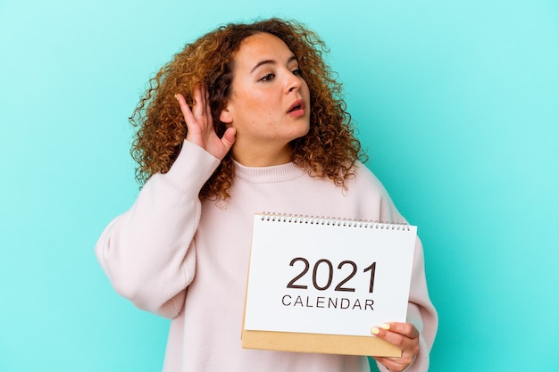 Young latin woman holding a calendary isolated on blue background trying to listening a gossip.
