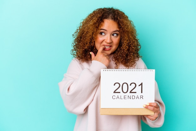 Young latin woman holding a calendary isolated on blue wall relaxed thinking about something looking at a copy space