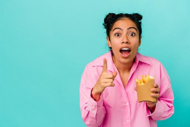 アイデア、インスピレーション コンセプトを持つ青の背景に分離されたチップを保持している若いラテン女性。