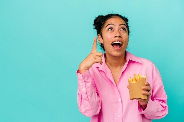 開いた口で逆さまを指している青い背景に分離されたチップを保持している若いラテン女性。