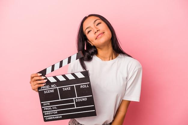 目標と目的を達成することを夢見てピンクの背景に分離されたカチンコを保持している若いラテン女性
