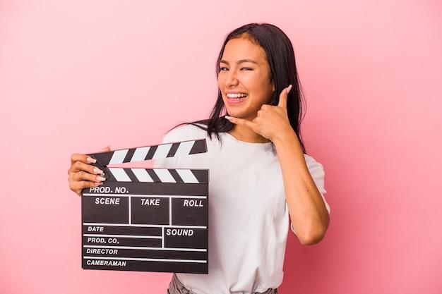 指で携帯電話の呼び出しジェスチャーを示すピンクの背景に分離されたカチンコを保持している若いラテン女性。