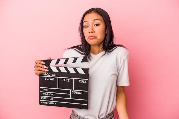 ピンクの背景に分離されたカチンコを保持している若いラテン女性は肩をすくめると混乱した目を開いています。