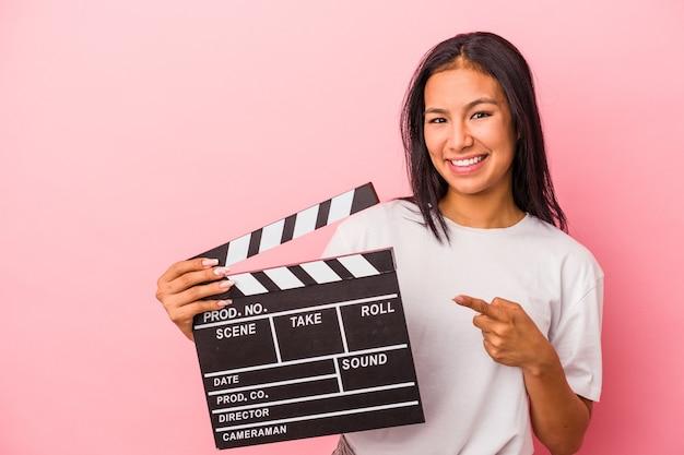ピンクの背景に分離されたカチンコを持って笑顔で脇を指して、空白のスペースで何かを示している若いラテン女性。