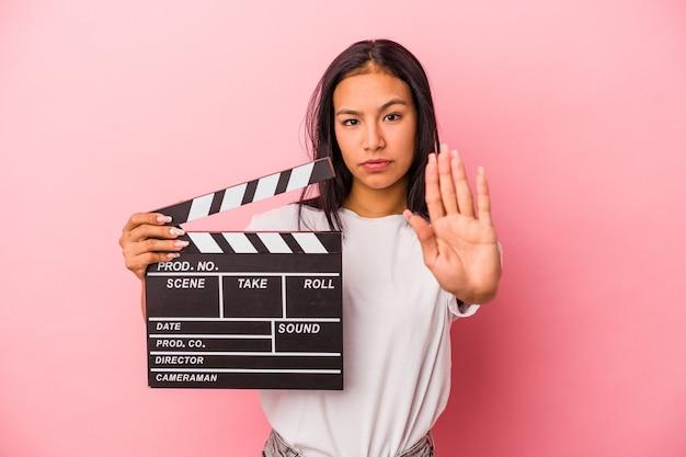 ピンクの背景で隔離のカチンコを保持している若いラテン女性は、一時停止の標識を示している手を伸ばして立って、あなたを防ぎます。