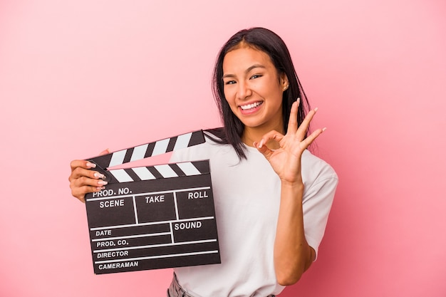 Young latin woman holding clapperboard isolated on pink background  cheerful and confident showing ok gesture.