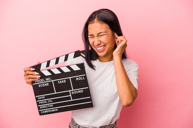 Young latin woman holding clapperboard isolated on pink background  covering ears with hands.